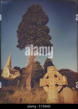 Old cross gravestone in graveyard in England - Stock Image