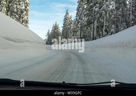Mountain road highway 88 towards Carson Pass, California, USA, on a winters day featuring five feet of snow on the side of the road after several stor - Stock Image