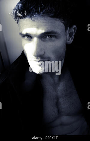 Black and white portrait of good looking man with pecs looking at camera - Stock Image