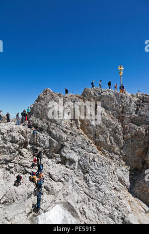 Tourists climbing to the Golden Cross - the highest point in Germany on the summit of Zugspitze at 2,962 m above sea level - Stock Image
