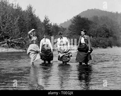 Four women hold up their skirts and enjoy the cool of a western river at the beginning of the 20th century, ca. 1910. - Stock Image
