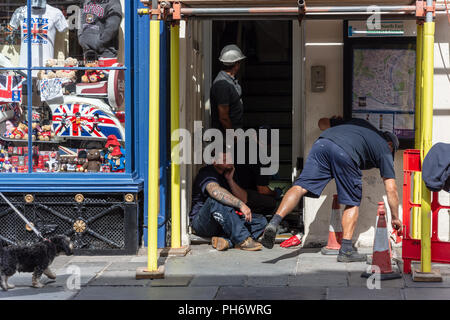 3 workmen in and around a doorway under scaffolding next to a shop selling British memorobilia in the city of Bath - Stock Image
