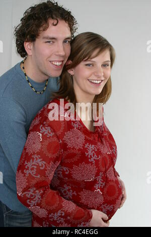 Pregnant couple  happy look at camecra, side, view, touching her belly - Stock Image