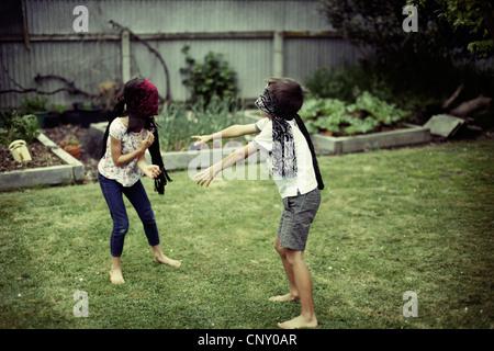 Children play wearing blinfolds. - Stock Image