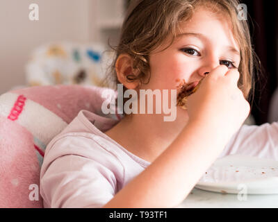 Small caucasian girl with long hair messy eating chocolate - Stock Image
