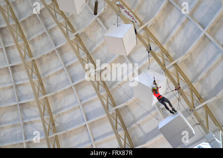 Climber climbing fake ice inside Devonshire Dome, Buxton, Derbyshire at adventure sports festival. - Stock Image