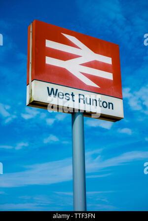 West Runton train station signpost against a blue sky. Norfolk, England, UK. - Stock Image