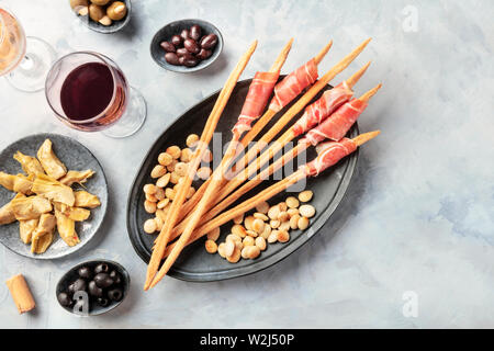 Italian antipasti. Grissini, parma, artichokes, olives, wine, shot from the top with copy space - Stock Image