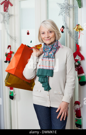 Senior Woman With Shopping Bags During Christmas - Stock Image