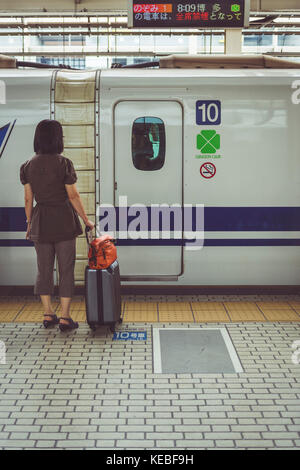 A traveller waits to board carriage 10 on a shinkansen bullet train - Stock Image