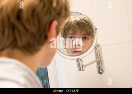 White teenage boy look at his reflection in a small bathroom mirror at his skin with a strip on his nose to get - Stock Image