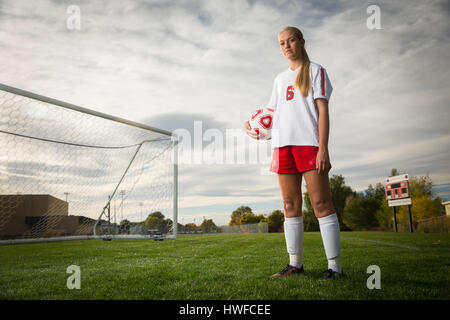 Low angle portrait of athlete standing with soccer ball on field under cloudy sky - Stock Image