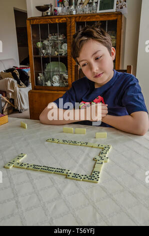A boy concentrates while playing a game of dominoes on a dining room table. - Stock Image