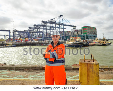 Dock worker at Port of Felixstowe, England infront of huge container ship - Stock Image