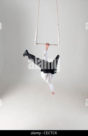 photograph of businessman hanging from trapeze swing - Stock Image