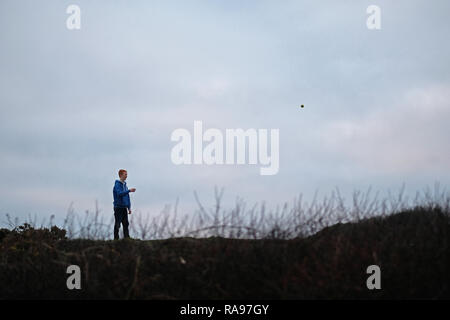 A teenage boy playing in a field. - Stock Image