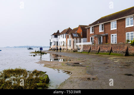 Houses with flood defenses on Shore Road still wet as tide goes out from Bosham creek in Chichester harbour. Bosham, West Sussex, England, UK, Britain - Stock Image