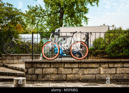 Bicycles including one with colorful pink wheels parked on a sidewalk in the NOtre Dame district of Paris France. - Stock Image