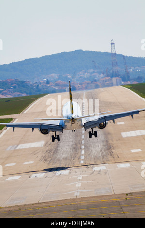Landing civil passenger airliner aircraft from back aiport visible runway - Stock Image