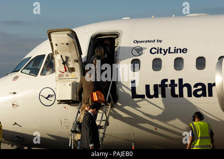 passengers with carry-on bags boarding a Lufthansa Regional BAE 146 Avro RJ-85 parked at London City - Stock Image