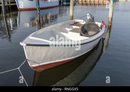 Small white fibreglass fishing boat with outboard motor, moored in harbour; Oester Hurup, Denmark - Stock Image
