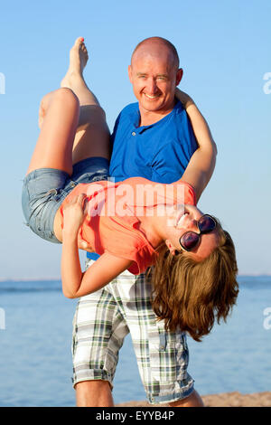 A happy couple having fun at the beach, on vacation - Stock Image