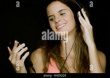 Young woman using smartphone and listening to headphones - Stock Image