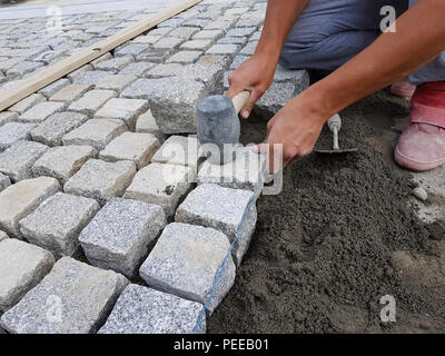 Construction worker arranging a pavement for renovating a street in an old city center - Stock Image