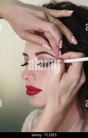 Makeup artist working in makeup studio, applies a brush on eyelid. Female face close up. - Stock Image