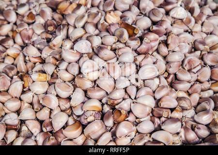 Pile of thai garlic cloves in a thai market. - Stock Image