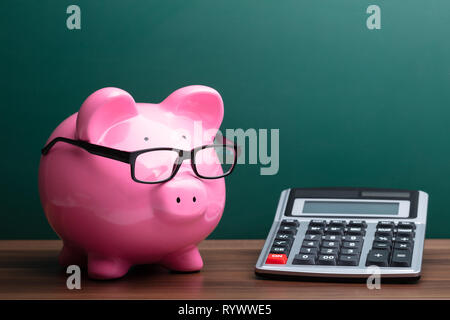 Calculator And Pink Piggybank With Eyeglasses In Front Of Green Board - Stock Image