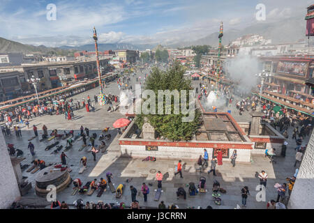 Morning view of crowded Barkhor square filled with juniper smoke, Lhasa, Tibet - Stock Image