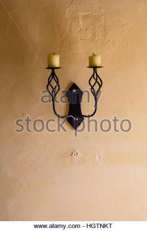 Black Steel Scrolled Candlestick Holders, with candles, on a wall in a French Home in Mantilly, Orne, France, Europe - Stock Image