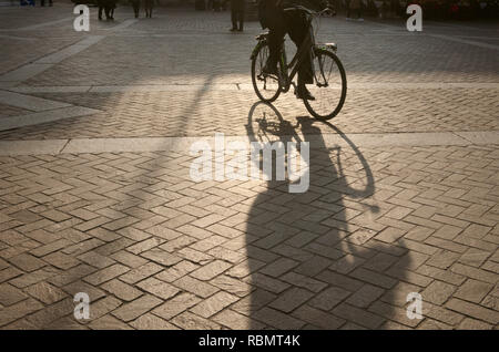 riding bicycle on a tiled square in Italy - Stock Image