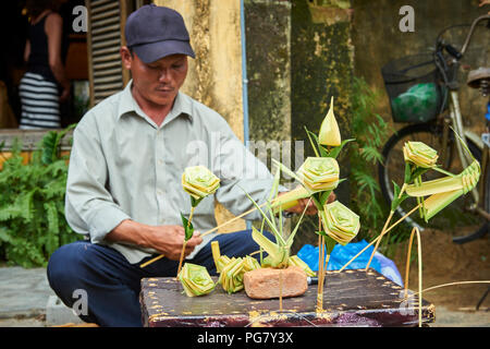 A talented street artist making and selling palm leaf roses in the streets of Hoi An, Vietnam. - Stock Image