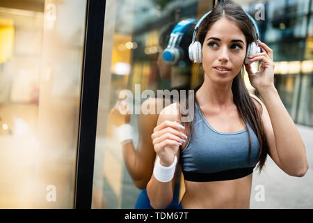 Young fit woman listening to music and working out by running - Stock Image