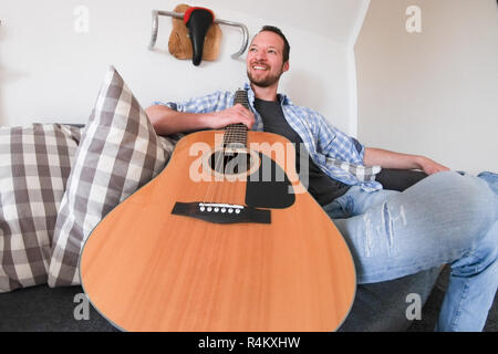 Young male with beard sitting on a sofa holding his acoustic guitar - Stock Image