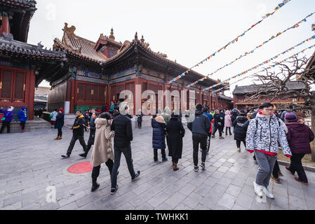 Tourists in Yonghe Temple also called Lama Temple of the Gelug school of Tibetan Buddhism in Beijing, China - Stock Image