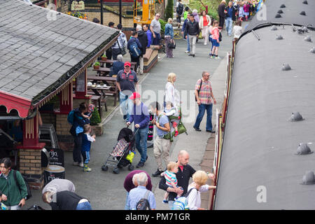 Busy train station platform at Haverthwaite preserved heritage railway in the Lake District as passengers disembark from the newly arrived train. - Stock Image