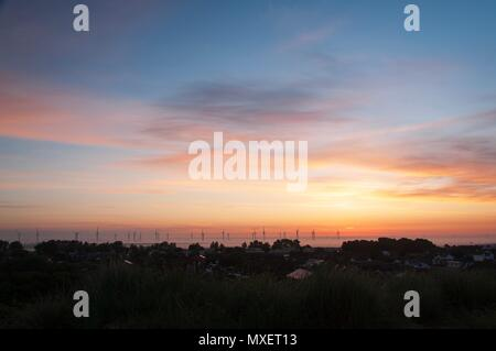 Wind turbines rising through the mist and silhouetted against the rising sun - Stock Image
