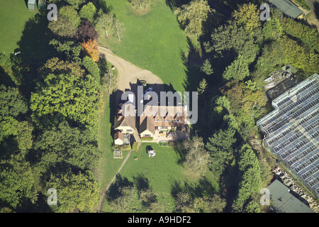 Aerial view of detached house in a rural setting with a large greenhouse in the grounds - Stock Image