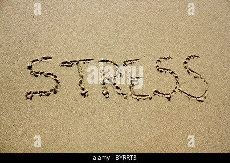 'Stress' written out in wet sand. Please see my collection for more similar photos. - Stock Image