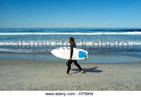 A surfer walks along the beach in Del Mar (San Diego County) in California, USA. - Stock Image
