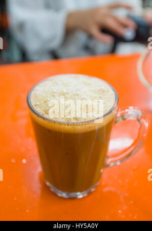 Malaysian milky coffee, commonly served in Indian cafes in this country, usually in glass mugs such as this. Glass - Stock Image