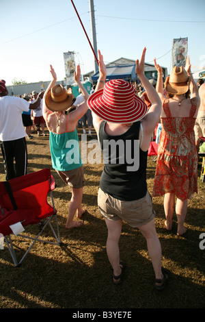 Three women applauding at the Fais Do Do Stage at the New Orleans Jazz and Heritage Festival, New Orleans, LA, USA - Stock Image