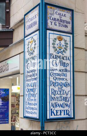 Gijon, Spain - 6th July 2018: Ceramic pharmacy shop sign on Calle Corrida. The street is the main shopping street. - Stock Image
