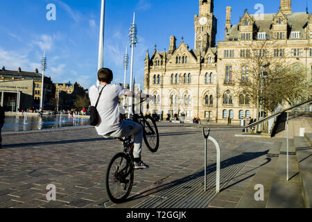 A cyclist 'wheelies' in the City Park with the Bradford City Hall, in the background. - Stock Image