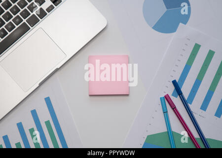 Business or education concept. Sticky note with copyspace, laptop, pens, paperwork on office desktop. - Stock Image