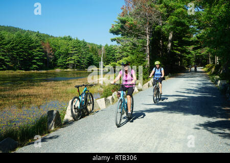 Two women riding their bikes on the Eagle Lake loop carriage road, Acadia National Park, Maine, USA. - Stock Image