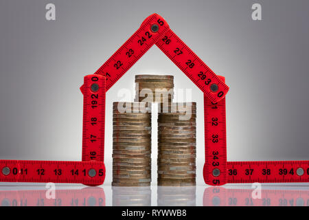 Stack Of Coins Under The House Made With Red Measuring Tape On The Desk - Stock Image